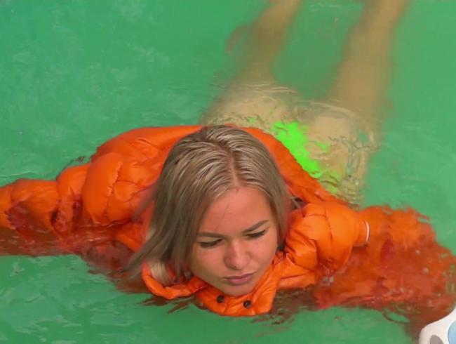 Video Thumbnail In oranger Daunenjacke im Pool schwimmen